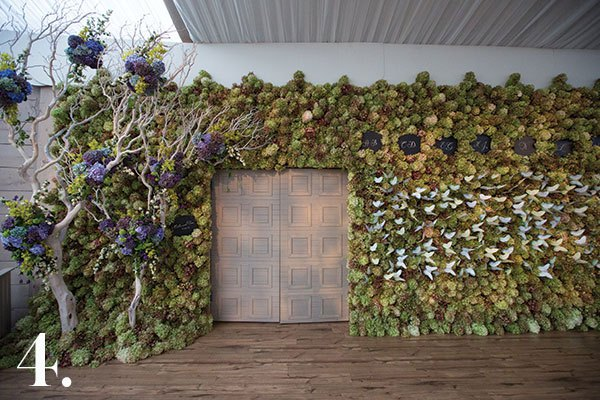 """The whimsical styling of this wedding was inspired by a display in the storefront of Mulberry in Paris. We covered the tent's 92-foot-wide exterior wall in varying shades of green """"PeeGee"""" hydrangea, and formed the illusion of an arched entry from 12-foot-tall manzanita branches dotted with periwinkle hydrangea. On the opposite side of the door, we pinned a flock of handmade, hand-painted butterflies to the wall. They were actually the place cards.