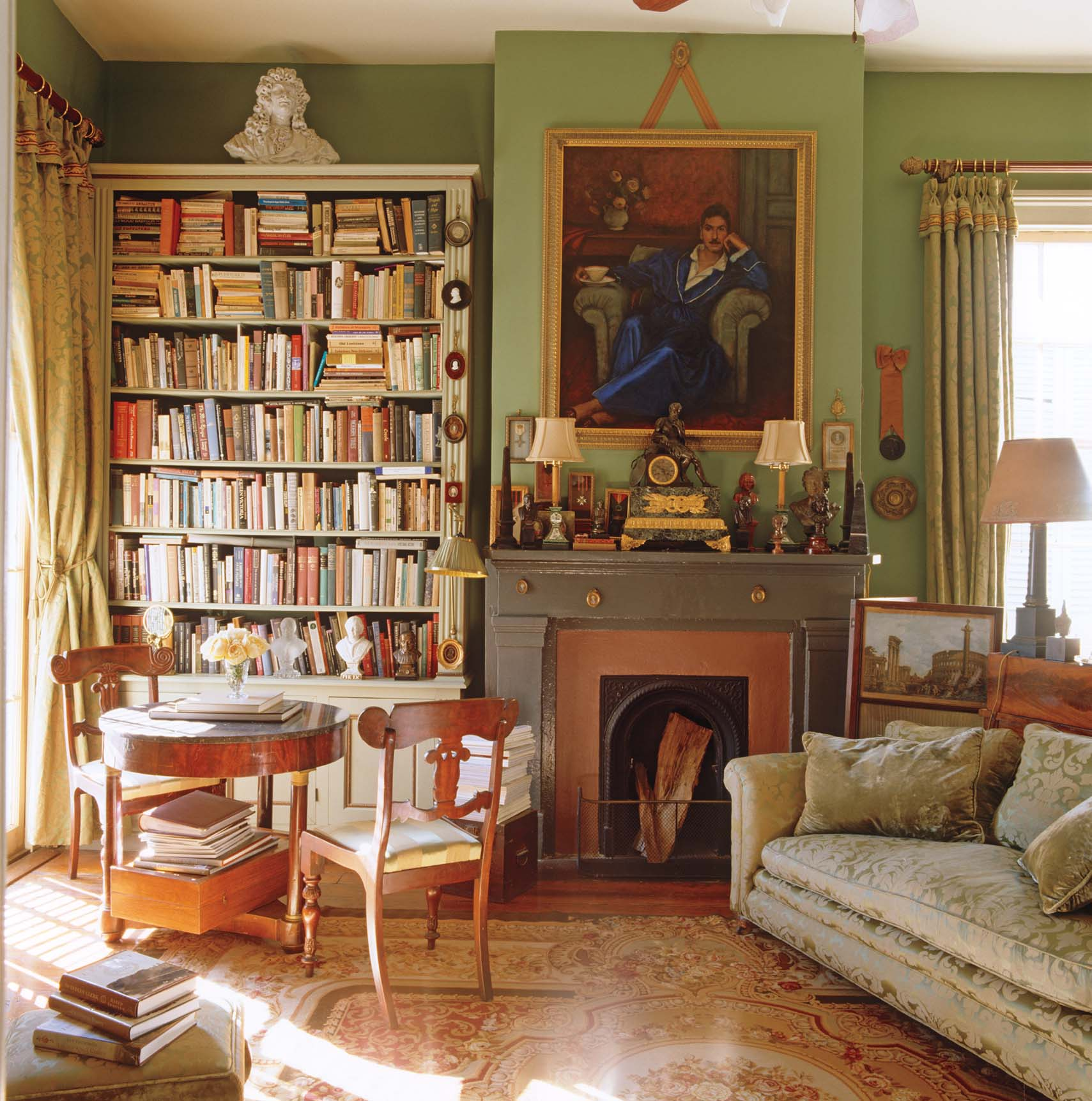 Patrick Dunne's home library is painted a soft green and is filled with sunlight by tall windows. A portrait hanging above the fireplace in the living room sets the tone for the library corner where a Biedermeier table and chairs provide a sunlit place to read