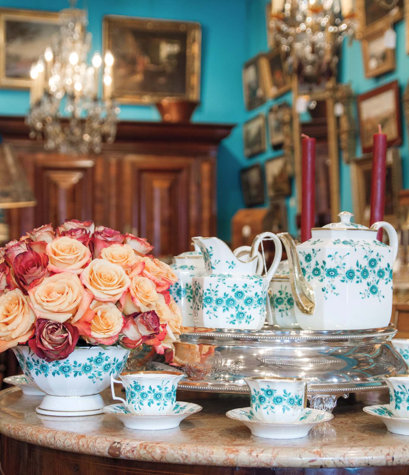 antique tea/coffee set with teal floral design on white porcelain. A rounded arrangement of muted pink and red garden roses fill a serving bowl