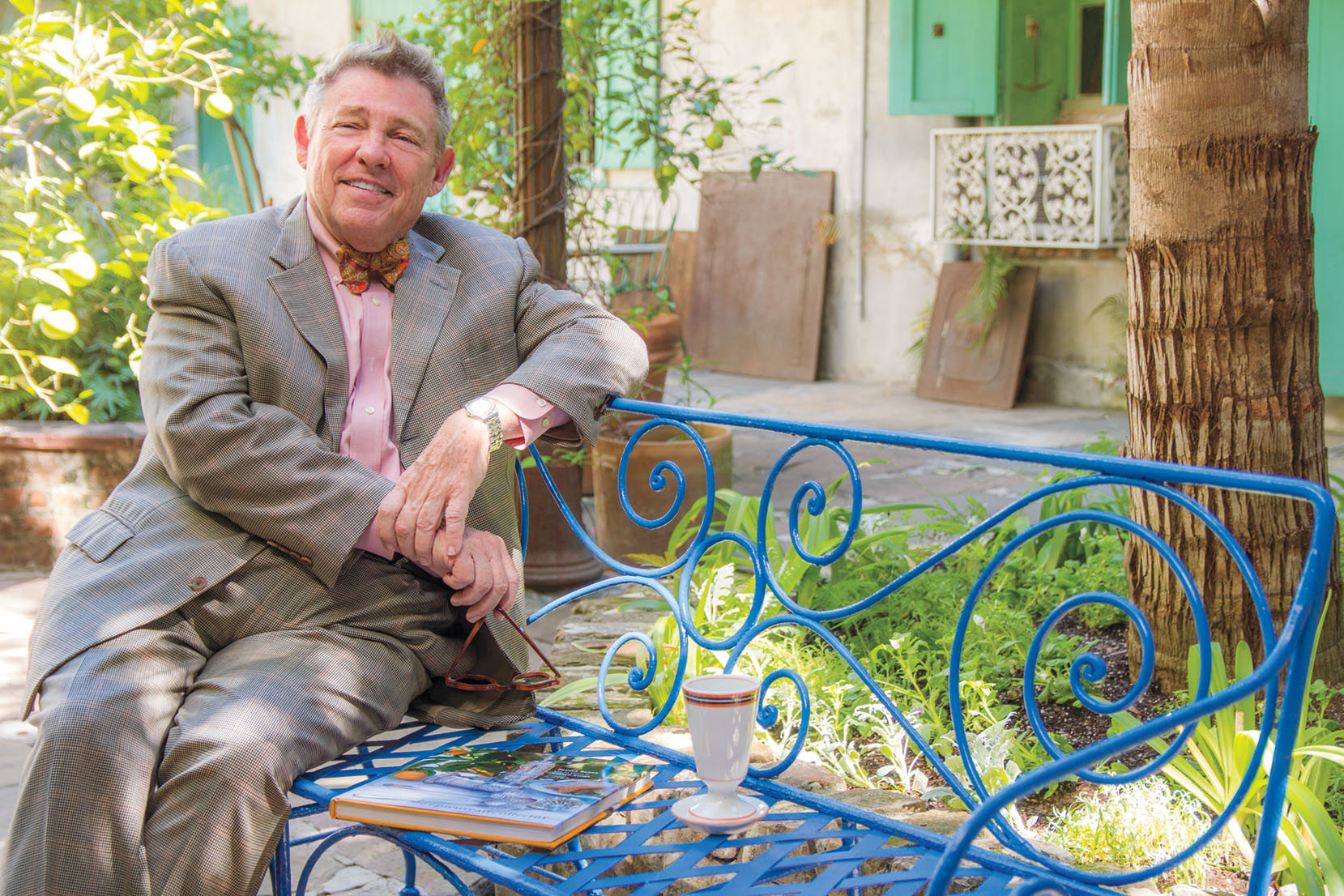Portrait of New Orleans interior decorator and antiques shop owner Patrick Dunne, wearing a gray suit with pink shirt, sitting outside a wrought-iron bench painted bright blue