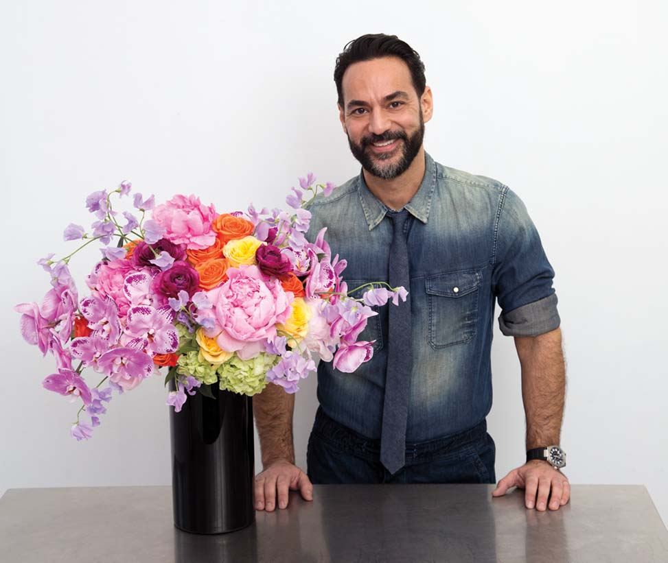 Floral designer Oscar Mora stands beside his finished flower arrangement