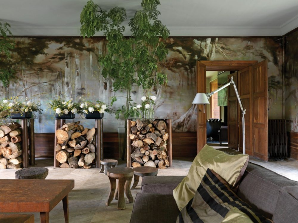 Claire Basler's salon features a woodlands mural that ensconces the room in natural hues. Stacks of fire wood stored under a trio of high tables echo the theme.