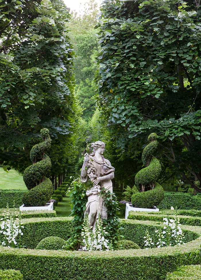 Carolyne Roehm garden parterre: In a precisely pruned shrubbery circle, lush vines climb a Classical-style statue of a woman, which stands in a bed of white foxglove flowers. In the background, two swirling topiaries mark the entrance to tree-lined path.