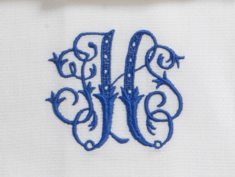 Traditional Three-Letter Monogrammed Napkin with orange embroider, featuring Leontine Linens with royal blue embroidery and scrolled letters