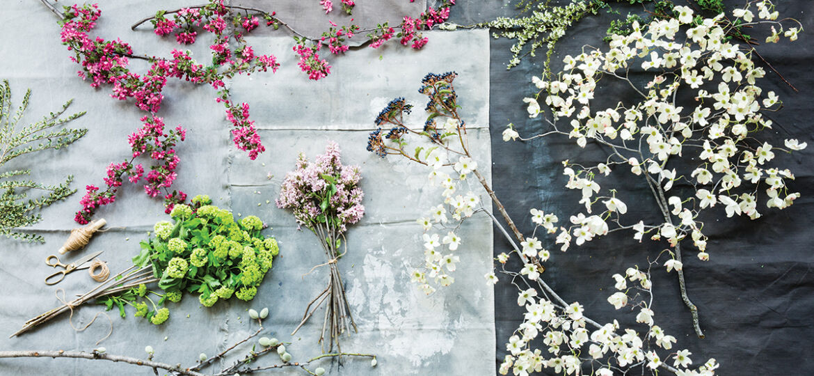 assorted flowering branches with white, green, hot pink, and light pink flowers, spread out on a wooden work surface