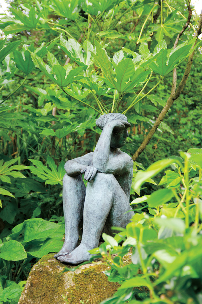 Abstract sculpture of a nude woman sitting on a rock