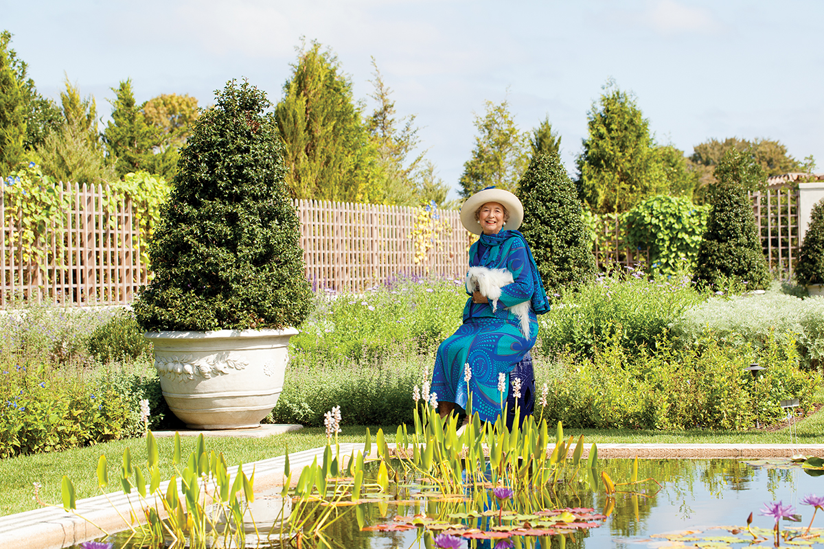 """A modern-day (2016) portrait of philanthropist/horticulturist Dorrance """"Dodo"""" Hamilton, wearing a blue dress and sitting by a garden pool in the Blue Garden, mirroring a classic portrait of the garden's original owner."""