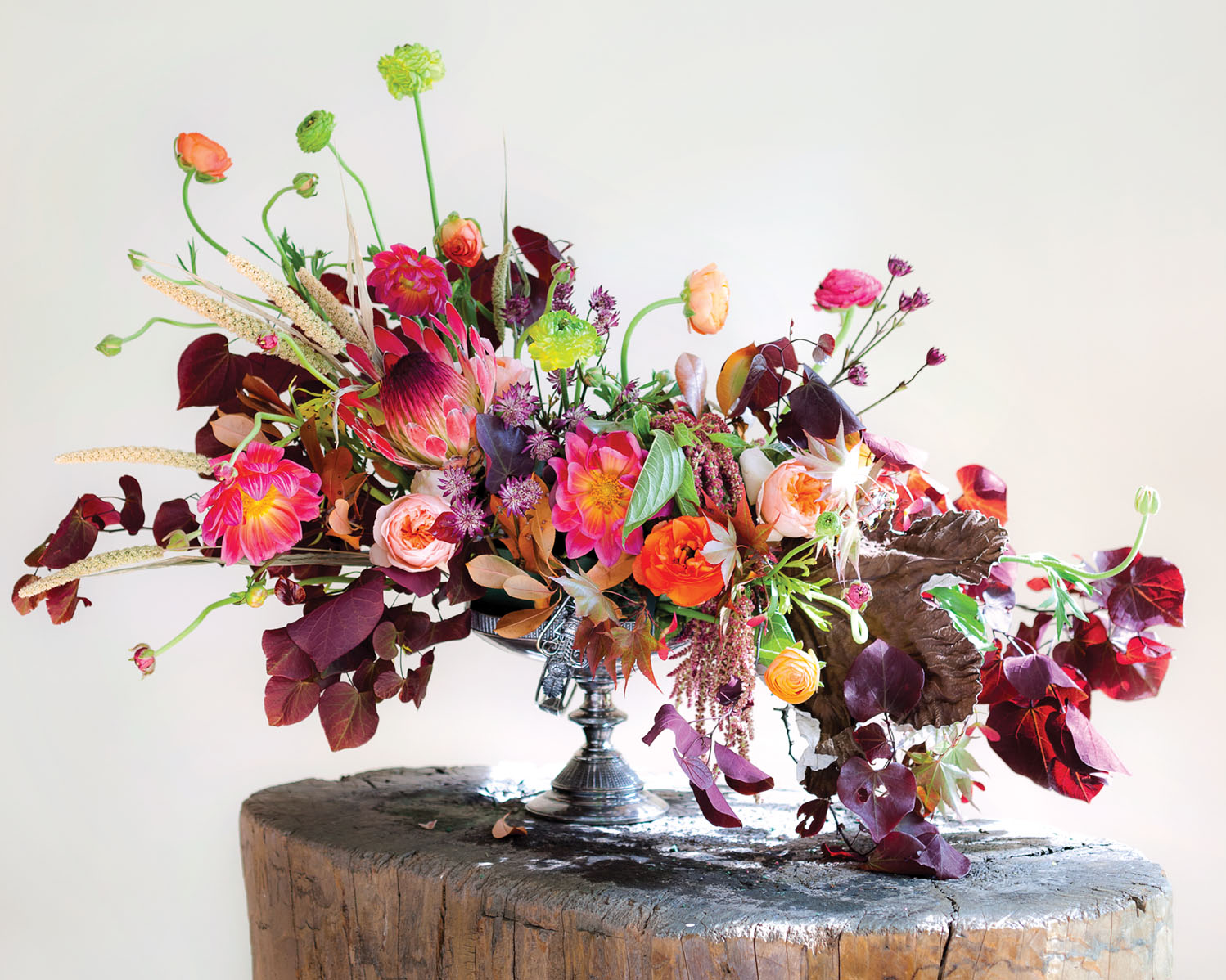S-curve floral design in a compote vase, featuring autumnal hues along with brighter pops of pink and green