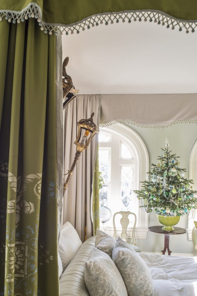 Pale green bedroom with rich olive green fabric canopy