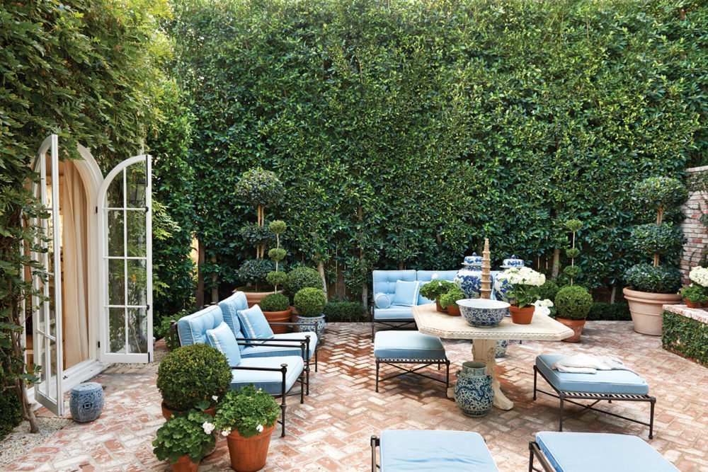 The brick patio is laid in a herringbone pattern. Black metal patio furniture with simple lines and blue cushions, as well as boxwood topiaries, surround a white plaster table at the center.
