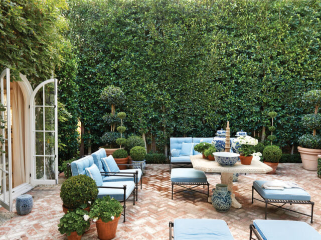 Designer Mark Sikes garden courtyard, surrounded in green living walls