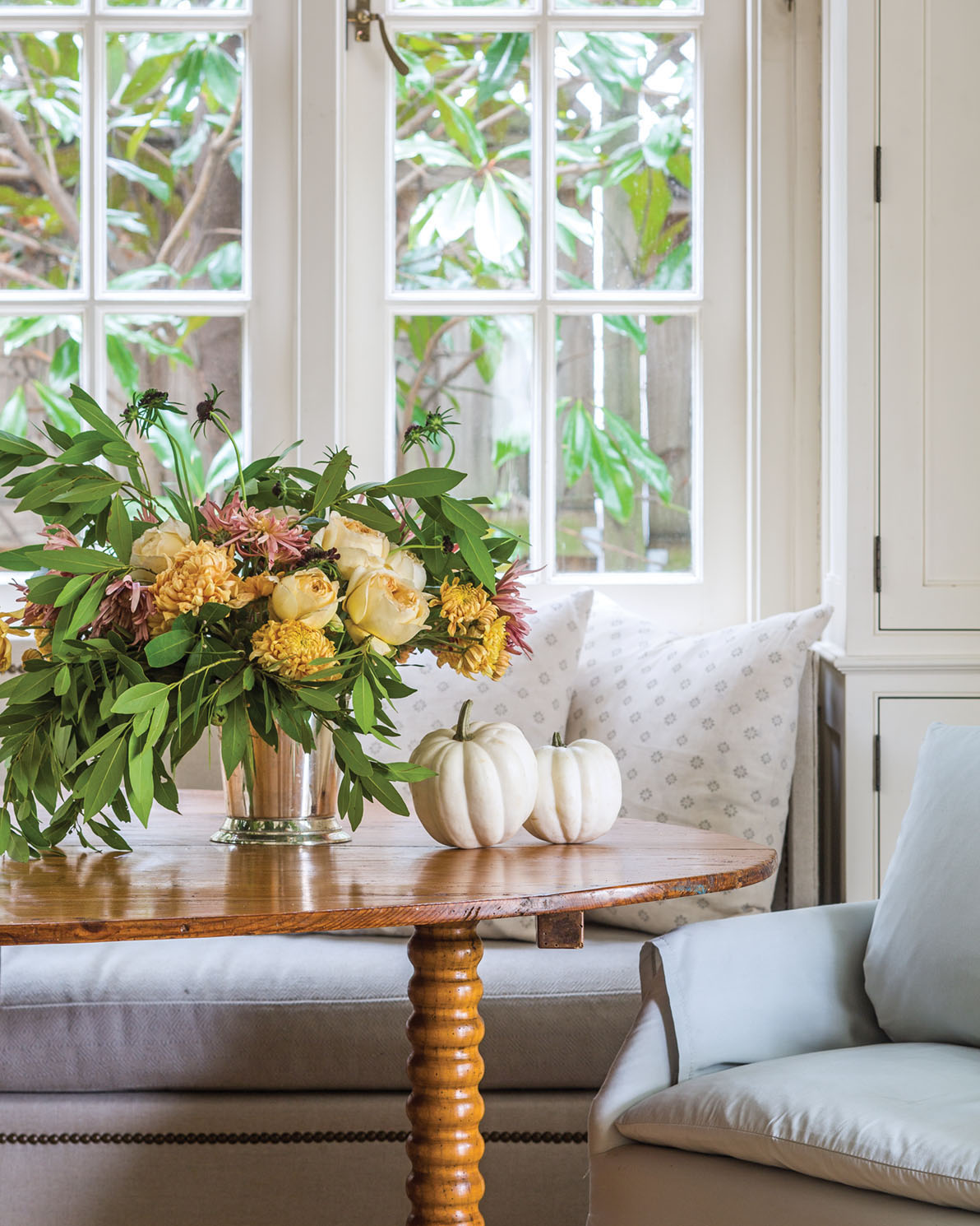 autumn arrangement on a breakfast table, displayed with two small white pumpkins. Seating includes an upholstered chair in pale blue and an upholstered banquette nestled into an window alcove