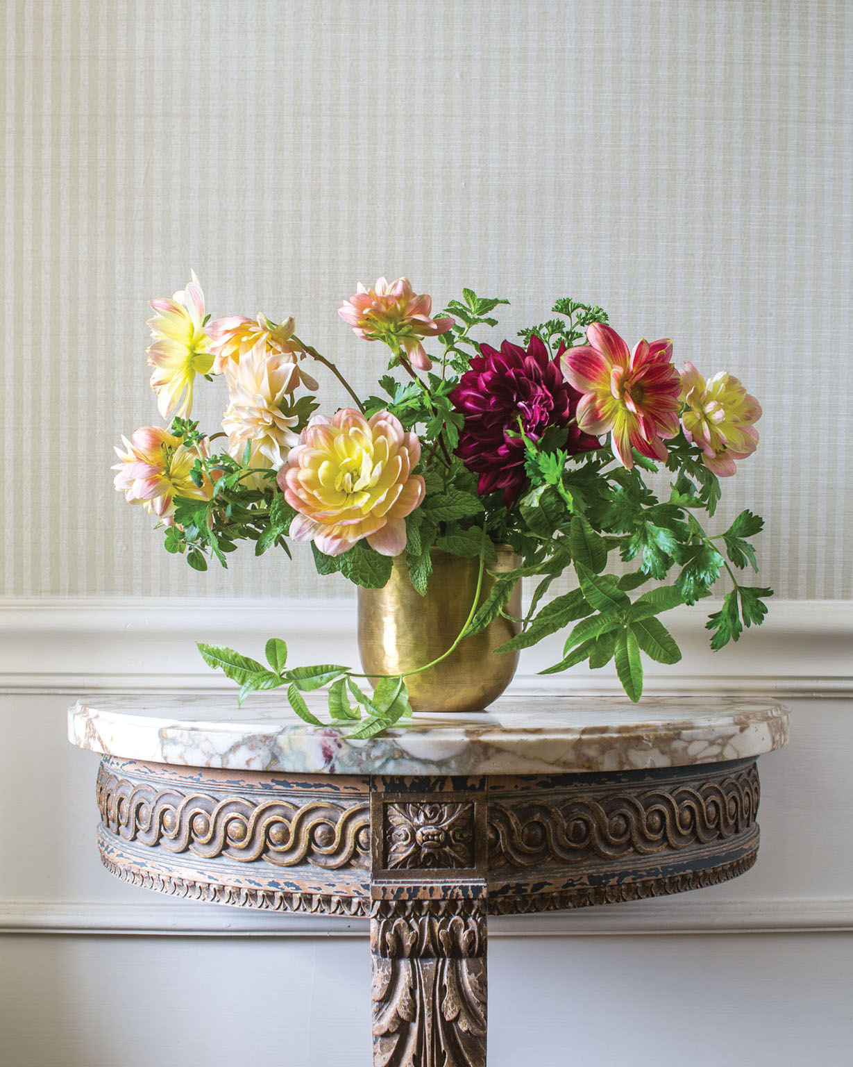 Sidra Forman's arrangement of autumn-hued dahlias with trailing herbs in a brass vessel, on a marble top occasional table with carved wood base, against a wallpaper of small taupe and white vertical stripes