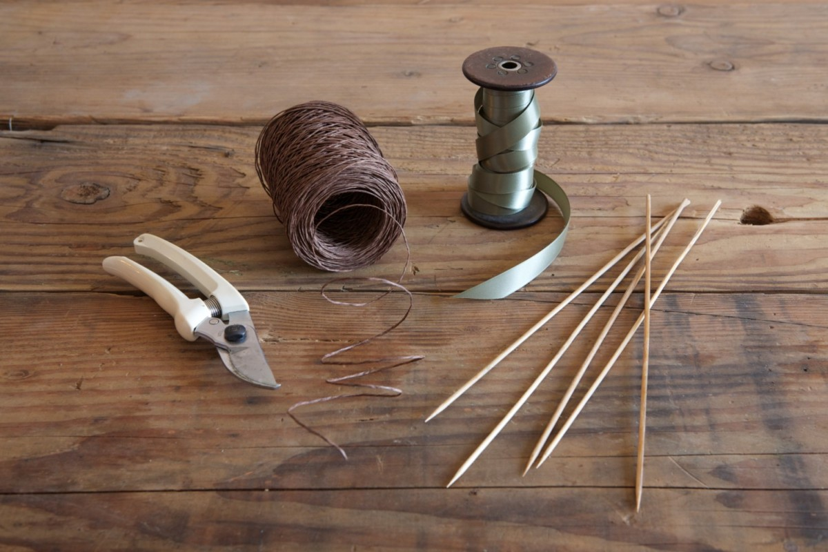 tools and supplies for Amy Merrick's festive wreath: clippers, twine, ribbon, skewers