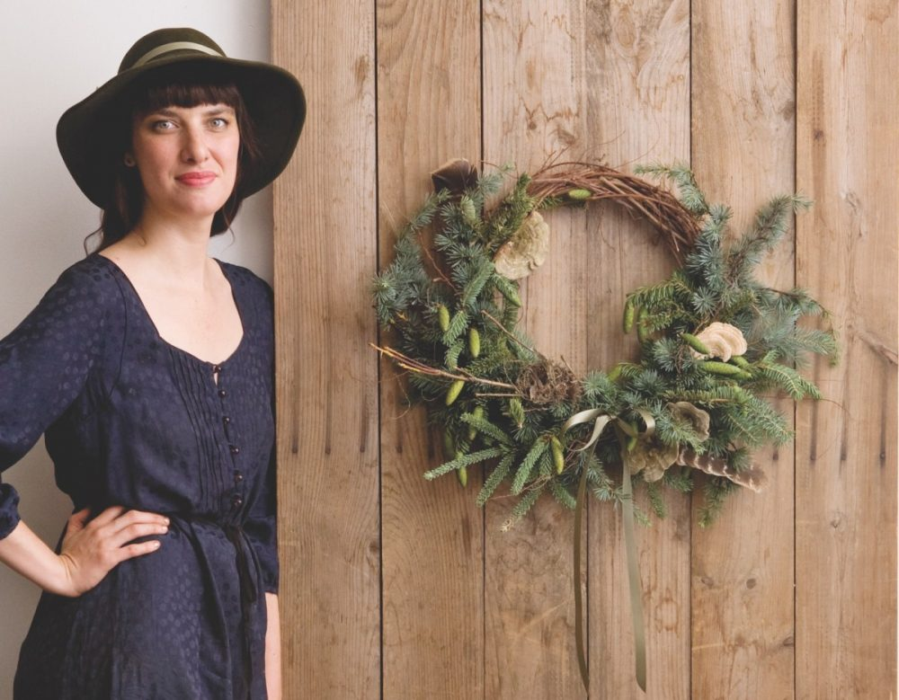 Floral designer Amy Merrick with long dark hair and short bangs, wears a navy sashed dress and a dark brimmed hat. She stands with her hand on her hip next to her evergreen wreath hanging on a barnwood wall
