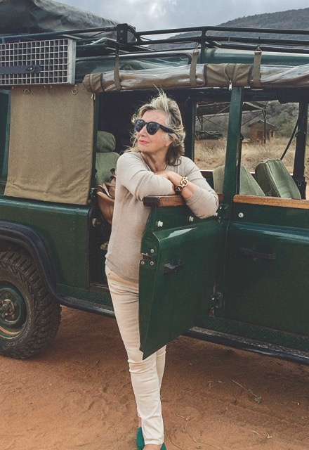 Sylvie Chantecaille stands by a green truck in the Africian countryside, wearing sunglasses, and a beige sweater, light pants, and deep turquoise flats