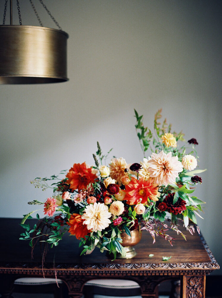 floral arrangement on an antique carved wood table beneath a cyndrical brass lamp