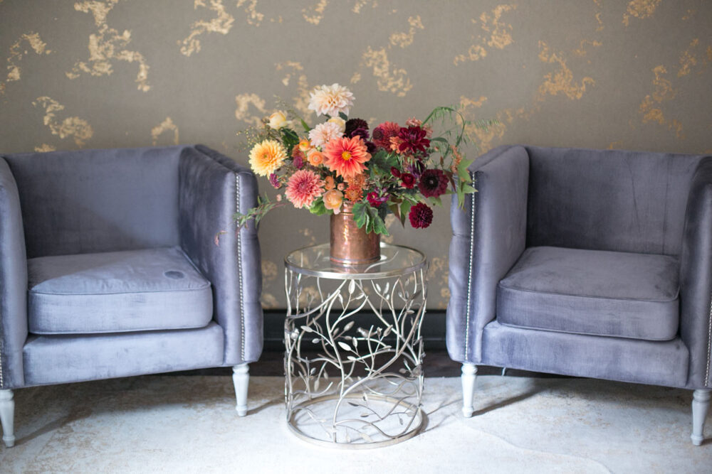A floral arrangement in a copper vessel stands on a small metal drinks table between two blue-gray velvet, square-shaped wing chairs. The wallpaper is gray with a metallic gold marbling.