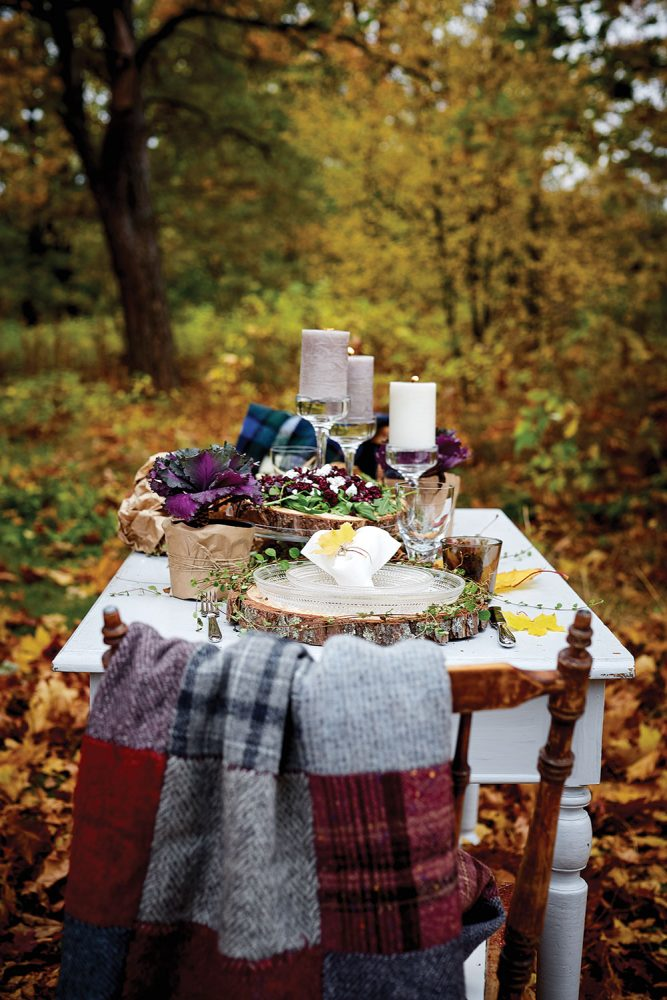 a potted ornamental cabbage, 2-inch thick cross sections of tree trunks used as platters, and pillar candles on glass pedestals are the table decor for the outdoor harvest celebration