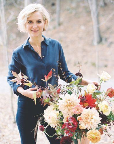 Denver, CO florist Frances Harjeet Grace of Prema stands next to a large autumn-hued arrangement wearing a dark blue blouse and a dark jeans