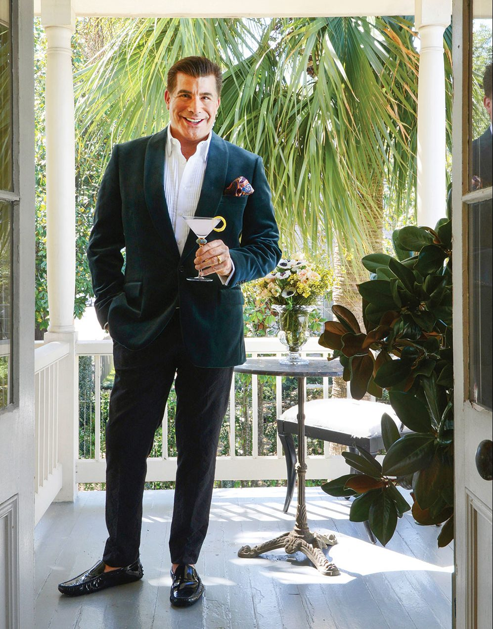 actor bryan batt stands on his covered porch, wearing a suit and holding a cocktail in a martini glass
