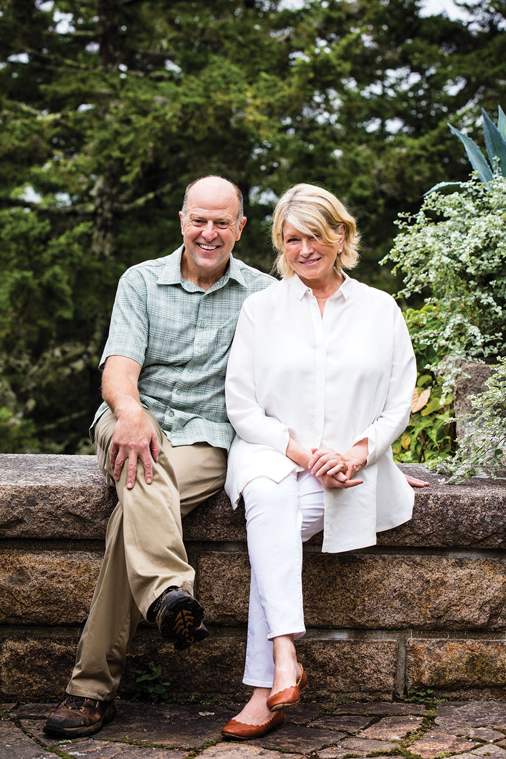 Martha Stewart and writer Daniel Hinkley sit outside on a low stone wall at Skylands, her summer home