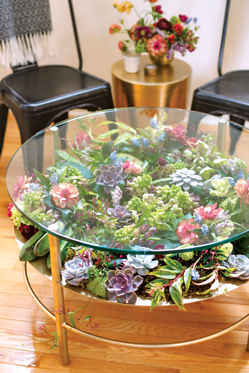 succulent arrangement under a round glass coffee table top with a brass base. Floral design by Susan McLeary