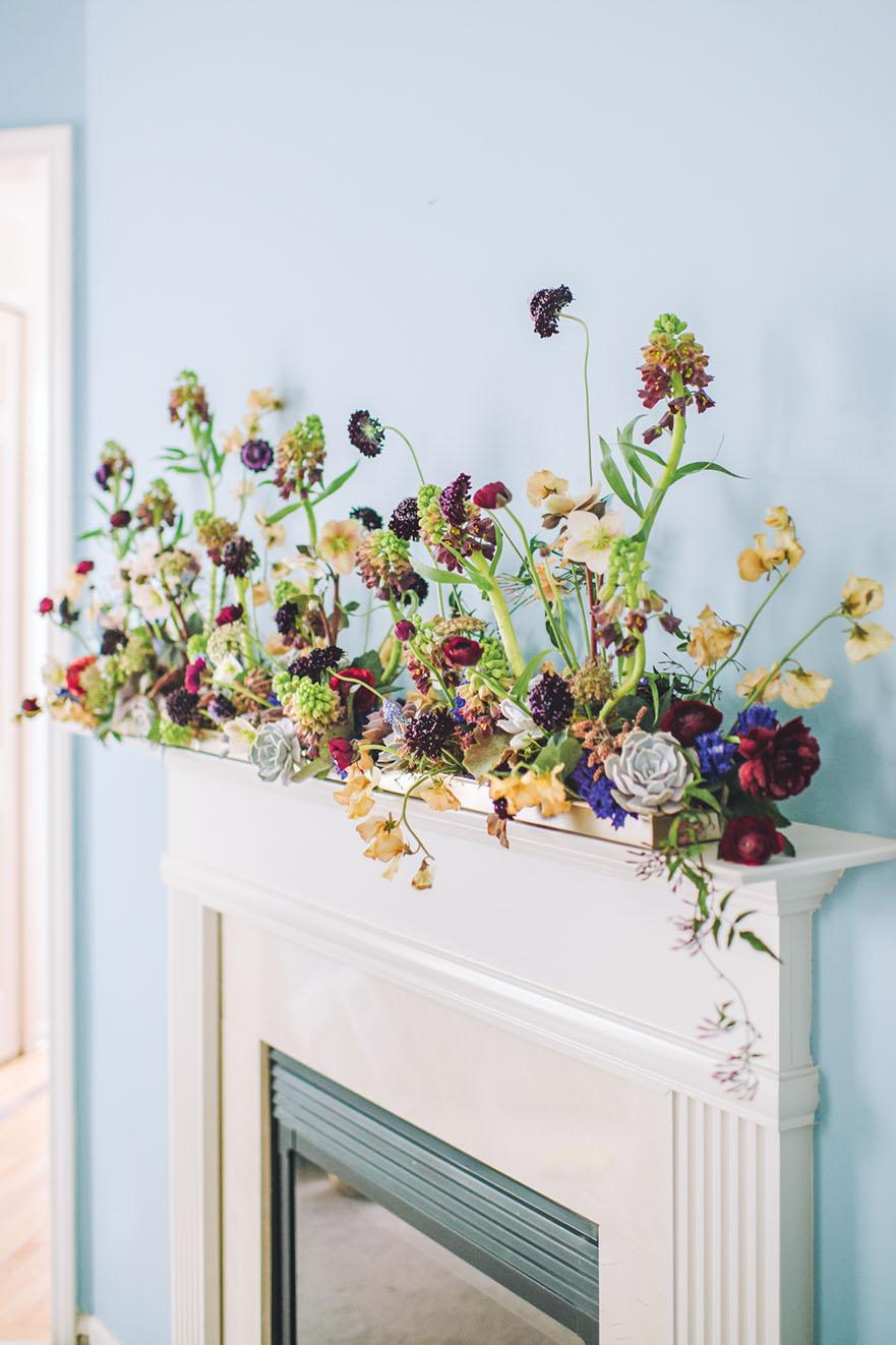 succulent and floral arrangement on a mantel
