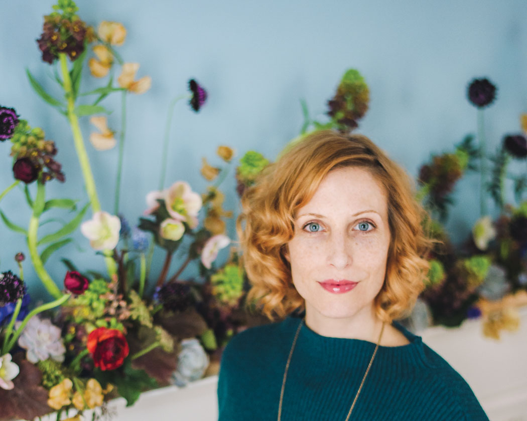 floral designer susan mcleary wearing a green sweater, standing beside a mantel she has decorated with succulents and spring flowers
