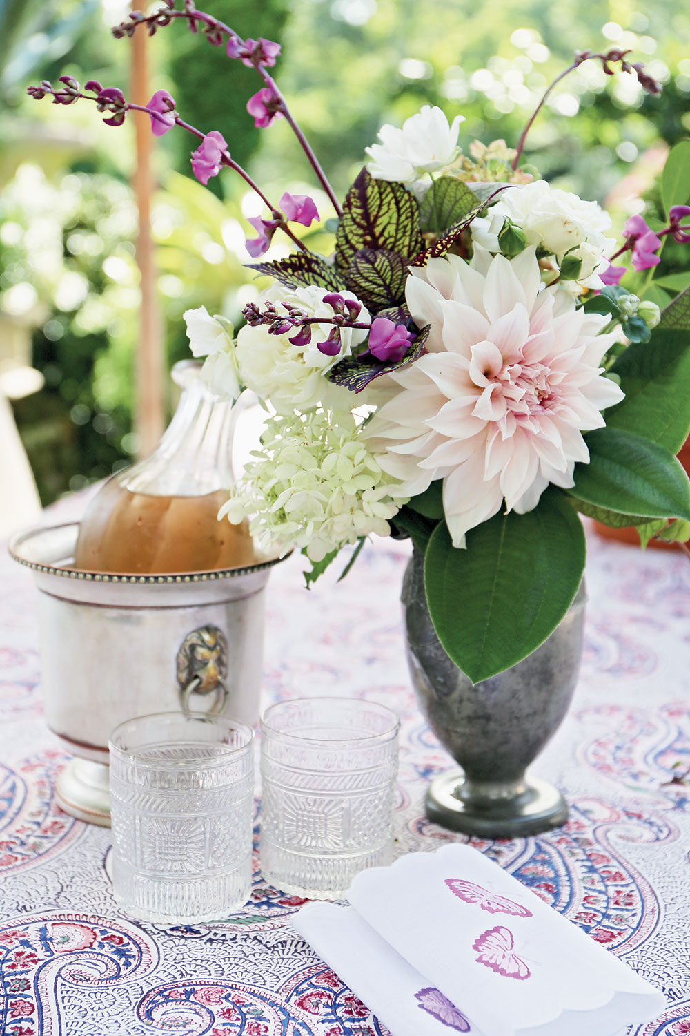 charlotte moss entertains, chilled champagne in an ice bucket, floral arrangement in a green vase, napkins, and glasses