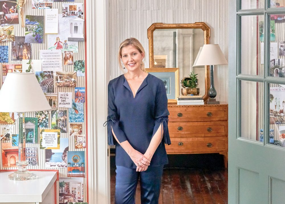 Tammy Connor stands by her inspiration wall in her Charleston office. The wall is upholstered in a Rogers & Goffigon ticking stripe.