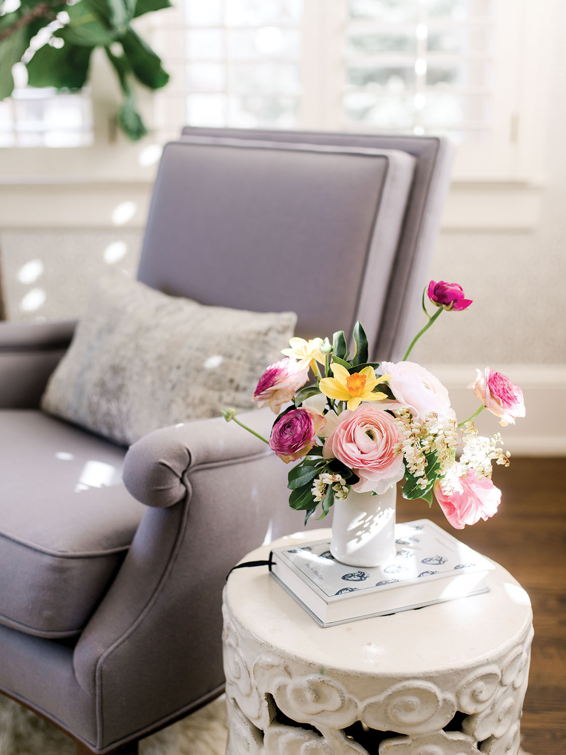 A white pottery garden stool serves as a side table beside an upholstered pale purple armchair in a room designed by Alecia Stevens