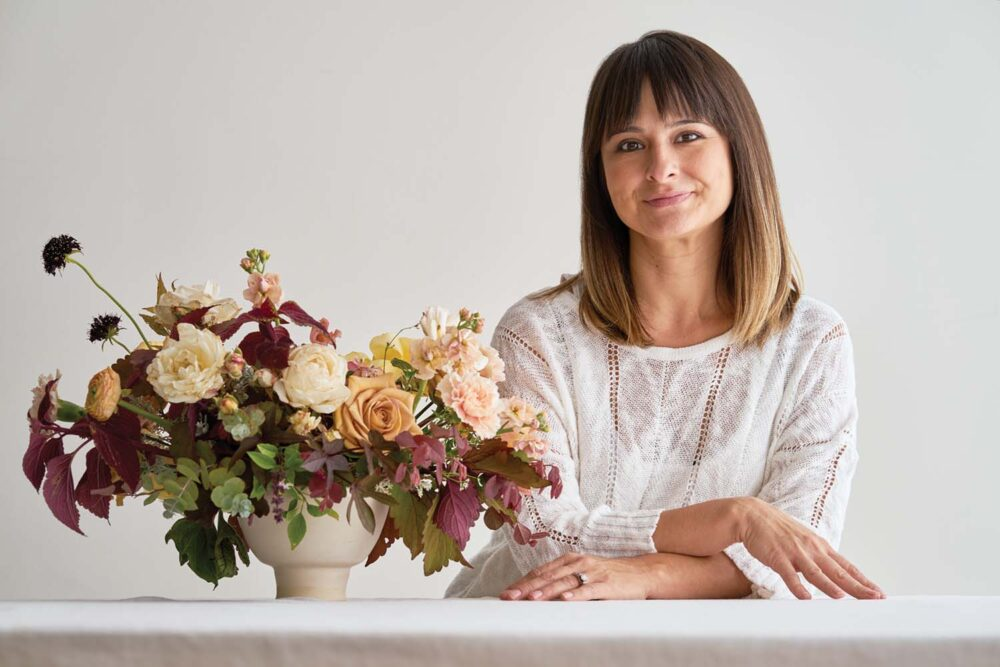 portrait of flora designer Adri Smith of Moss Floral, wearing a white top and shoulder length hair with bangs. She leans on a white counter next to her finished arrangement, with her arms resting crossed on the counter surface