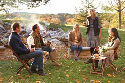 Friends gathered around a fire for a fall party