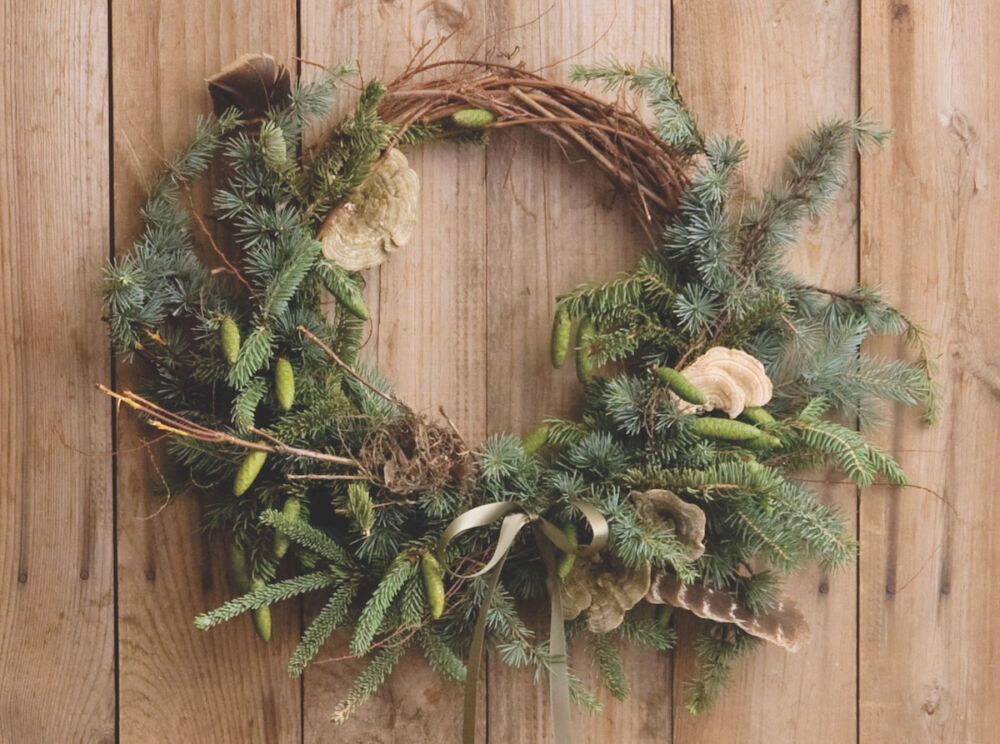 Evergreen wreath embellished with fir, blue spruce, weeping blue spruce, a bird's nest, turkey feathers, dried spirea branches, and dried lichen. The top third of the grapevine wreath base remains exposed.