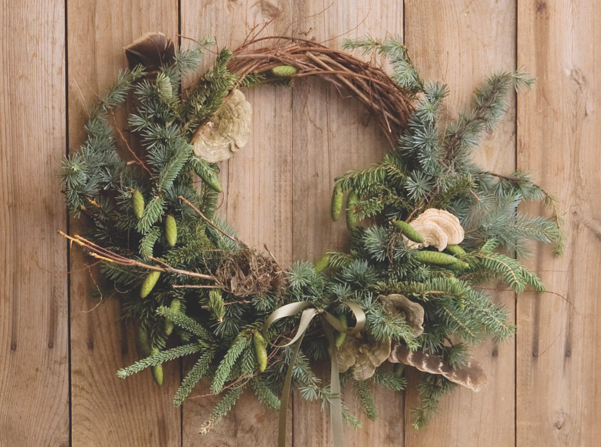 Festive Wreath by floral designer Amy Merrick featuring a grapevine form, several types of evergreen, turkey features, lichen, and a foraged bird's next