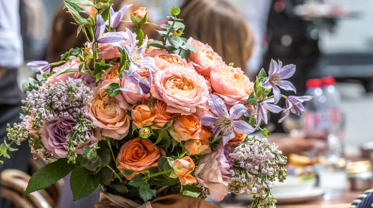 A French-style bouquet of peach and purple blooms sits on an outdoor table at a cafe in Paris
