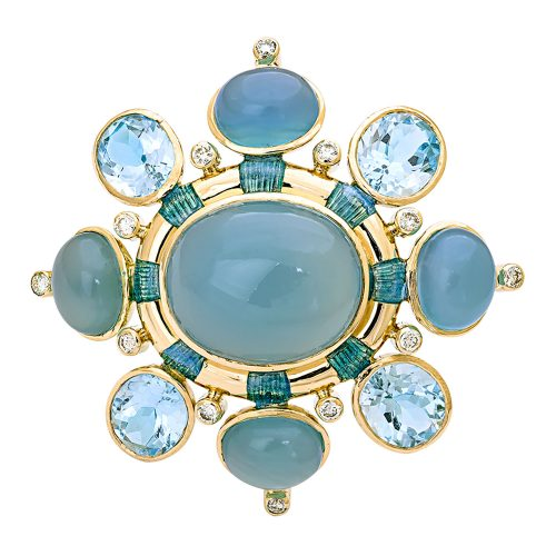 Photo of brooch featuring a large gray-blue oval center stone in a gold setting, ringed in 8 small diamonds and 8 stones alternating chalcedony and topaz
