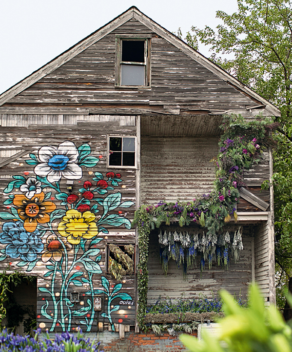 Dilapidated wood-frame house featuring a flower mural and adorned with plants
