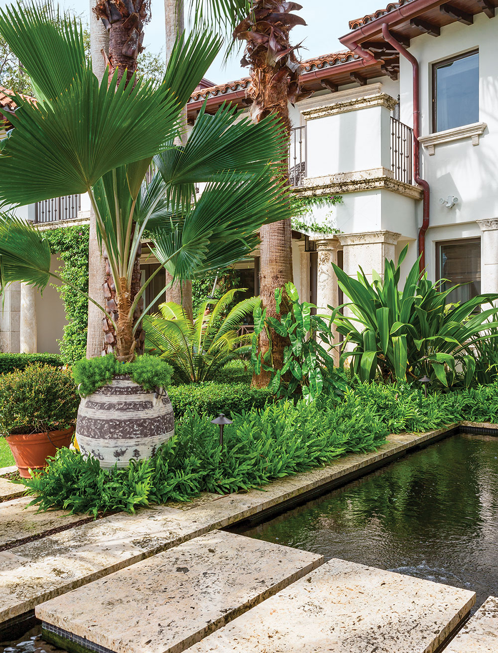 Limestone slabs create a path over ponds that house the owners' collection of Asagi and Shusui koi. The urns are from Authentic Provence in West Palm Beach.