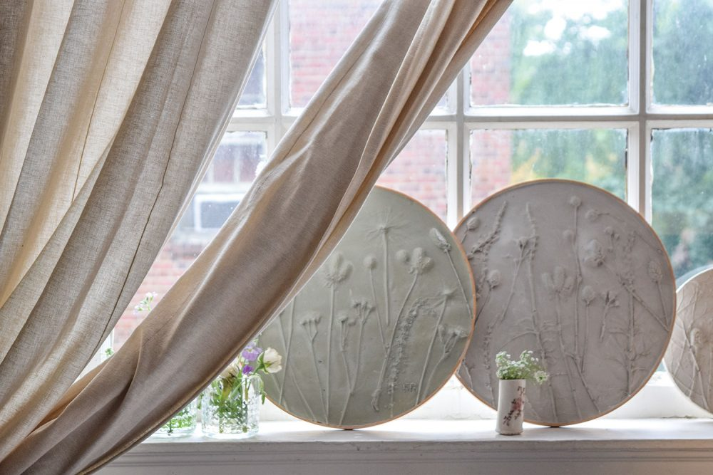 Three circular Ron Nicole pieces stand on a window sill with a college of bouquets in small porcelain and cut-glass vases. There's a muslin curtain tied back, and the window is an older style with grilles.