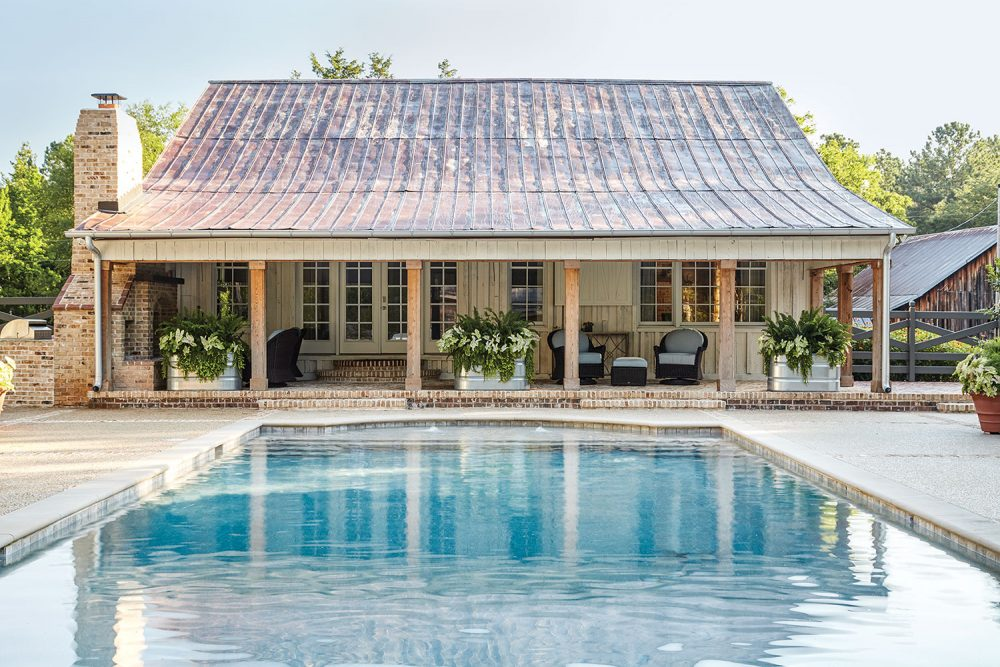 A blue pool leads to a covered brick patio of the pool house, which features wood columns across the front and an aged metal roof and brick chimney