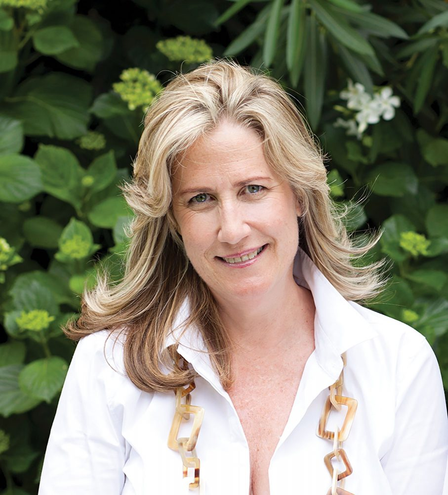 Portrait of Debby Tenquist, founder of Botanica Trading. She has blond hair and blue eyes and wears a white blouse and chunky tortoise shell necklace