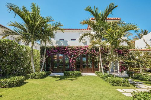 Photo of white stucco home with tile roof. The garden designed by Fernando Wong features a an expanse of open green lawn and palm trees. The first story of the side of the house facing the garden is covered in blooming bougainvillea.