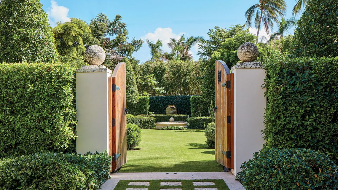 Photo of a Palm Beach Garden designed by Fernando Wong, surrounded by a high hedge. The heavy wood gate doors are open, lending a view inside of the manicured lawn, hedges and in the background a large urn.
