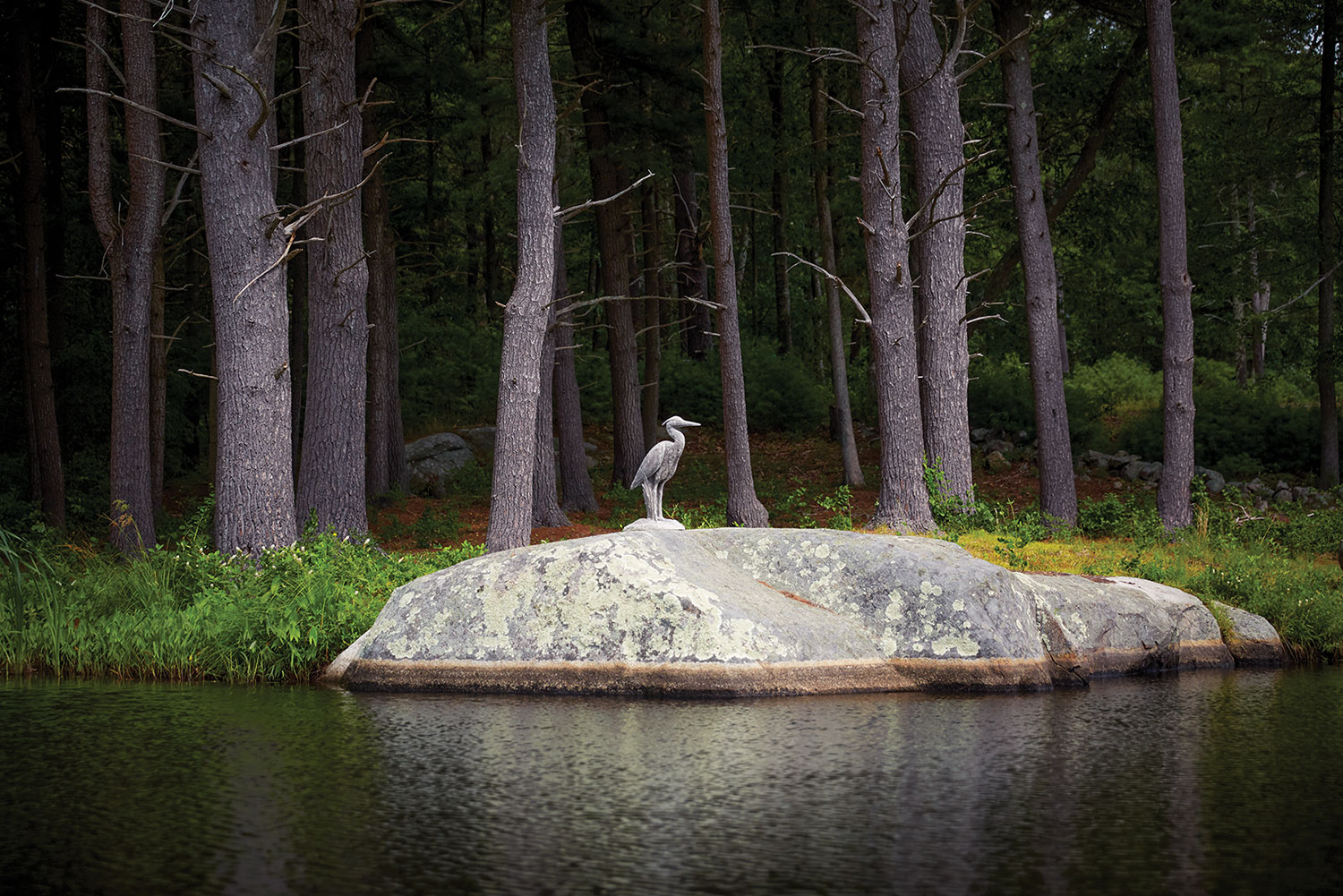 The statue stands on a large rock at the edge of a body of water. In the background is a dense forest.