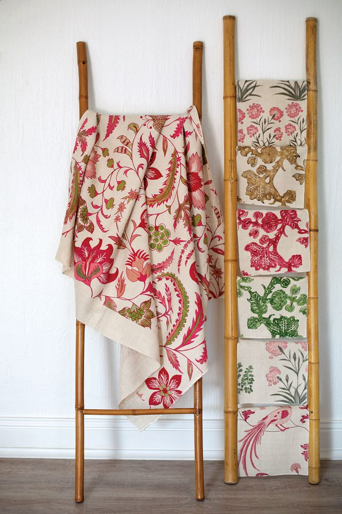 Assorted pink and green botanical print textiles, designed by Debby Tenquist of Botanica Trading, hang on bamboo display racks