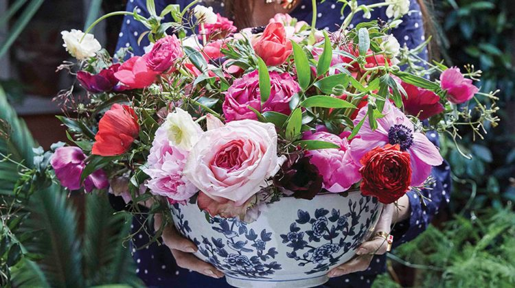 a blue-and-white bowl of flowers in shades of pink featuring