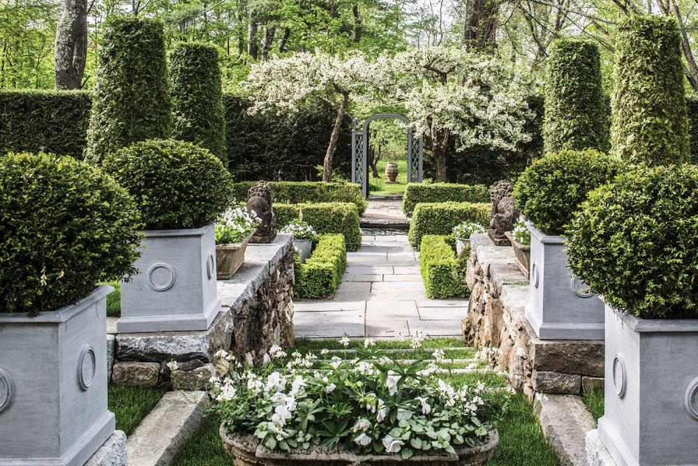 View through the center path of a formal garden filled with shrubs trimmed into geometric shapes, such as spheres, columns and square boxwood borders. The Pennoyer Newman Circle Icon Planters are square and several feet high and wide. In the distance, you can see an arbor leading to the exit, which is framed by a small flowering tree or shrub.