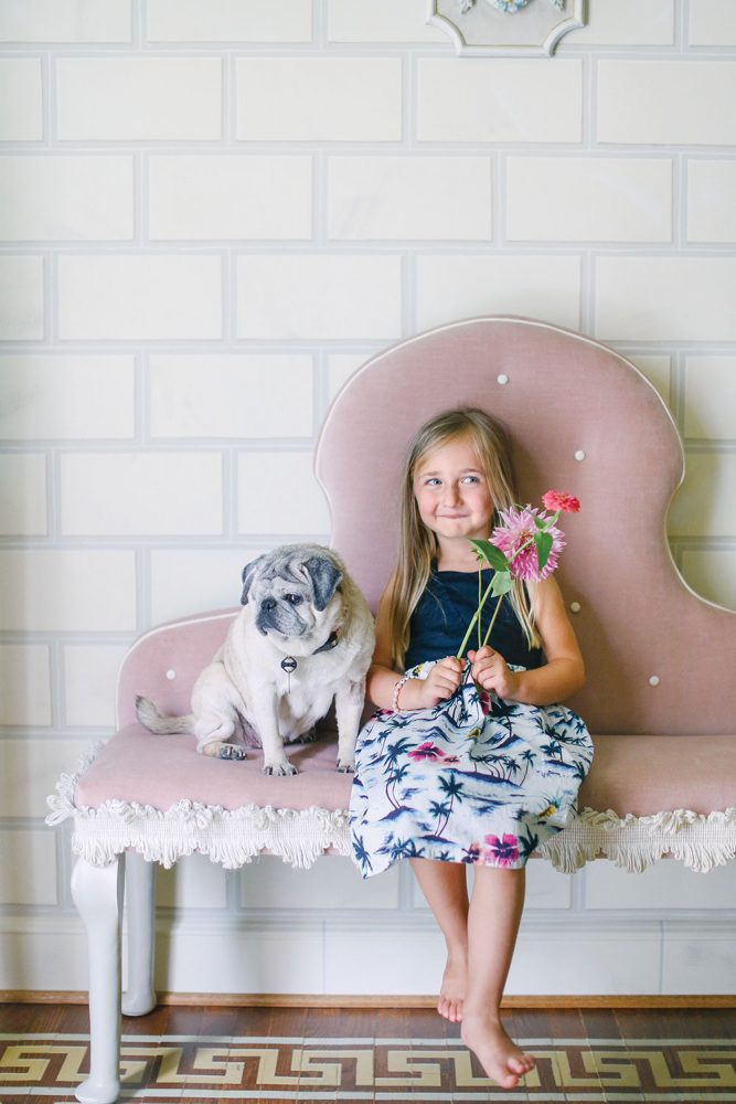 A little girl, who holds fresh flowers in each hand, sits on a pink upholstered bench beside a pug in Jason Oliver Nixon and John Loecke's home in High Point, North Carolina